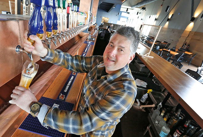 Owner Scott Cooper of Cohasset fill a glass with a lager. Let's Eat- Flanders Field in Hanover is a European themed beer hall on Sunday February 28, 2021 Greg Derr/The Patriot Ledger