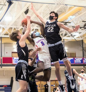 Winnacunnet's Elynn Houston drives to the hoop between Exeter's Evan Pafford (15) and Jacob Gibbons in last week's Division I boys basketball game. The two teams will meet on Thursday in Exeter in the Division I tournament.