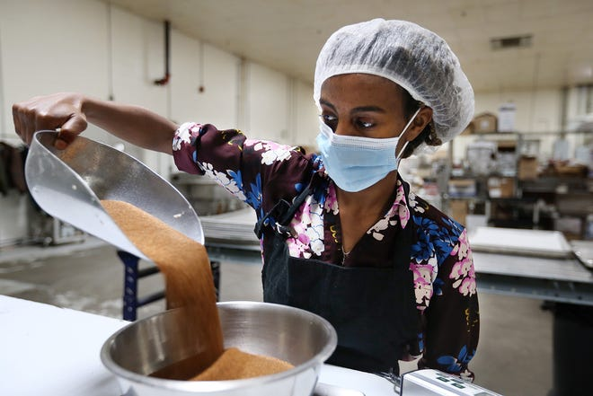 Saron Simon Mechale measures out teff grain in the kitchen at her Providence startup, goTeff, which makes and sells a nutritious snack crisp made from the grain, a staple food in her native Ethiopia.