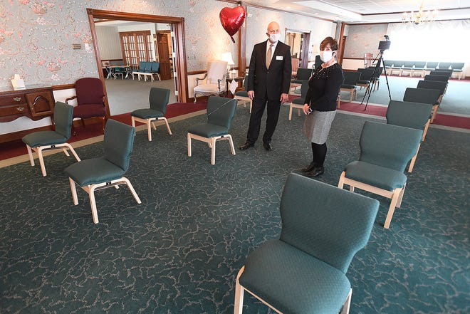 John Christian, co-owner of Cassaday-Turkle Christian Funeral Home in Alliance, and Nancy Castellucci, a funeral director, separate chairs six feet apart for services as a precaution during the COVID-19 pandemic. The funeral home allows those who cannot attend services to attach well wishes to balloons that are affixed to otherwise empty chairs.