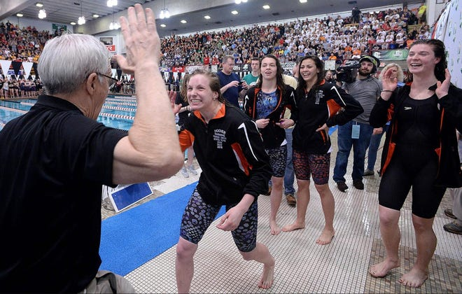 Hoover coach Rick Morrison presents the gold medals to the Vikings 200 record-setting free relay consisting of Parker Timken, Caroline Ehlers, Amanda Palutsis and Kate Lochridge at the 2018 OHSAA Division I Swimming State Finals at C.T. Branin Natatorium.