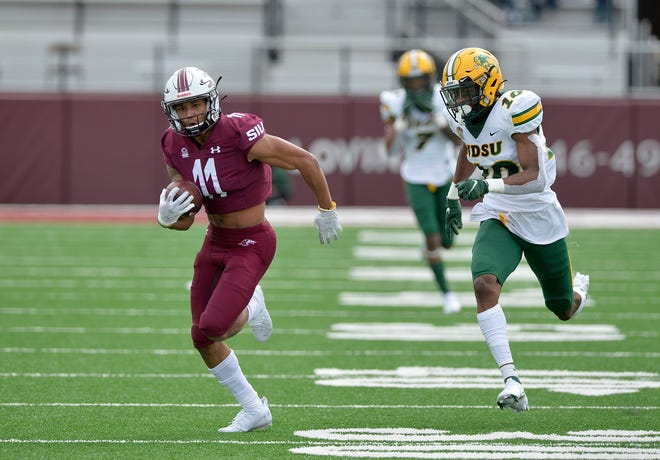 Southern Illinois wide receiver A'vanté Cox (11) sprints away from North Dakota State safety Dom Jones (10) on a 65-yard reception during the second quarter Saturday in Carbondale. [Byron Hetzler/The Southern Illinoisan via AP]
