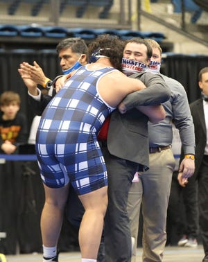 Manhattan's Damian Ilalio gives a hug to Indian assistant coach Danny Grater after capturing the 285-pound state title at Saturday's Class 6A state championship at Hartman Arena.