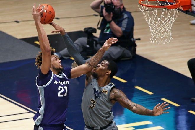 Kansas State forward Davion Bradford, left, goes up for a shot as West Virginia's Gabe Osabuohien defends during the first half Saturday in Morgantown, W.V.a.