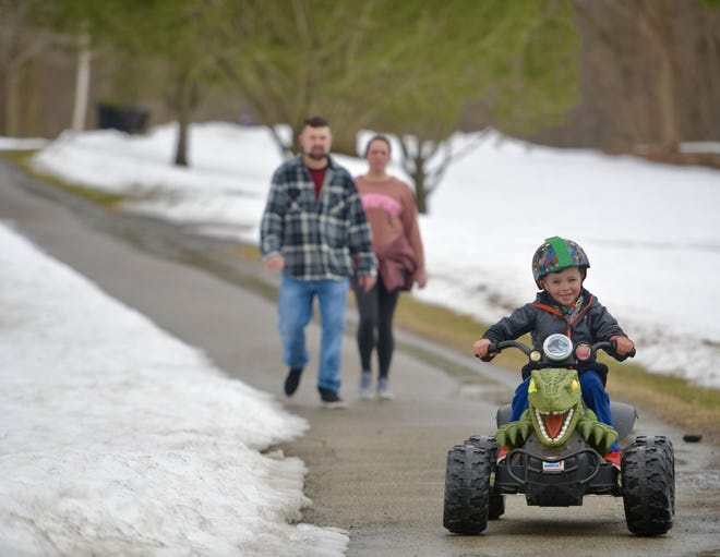 WORCESTER - Watchful parents follow behind their son as he rides a dinosaur car through Green Hill Park on Sunday.