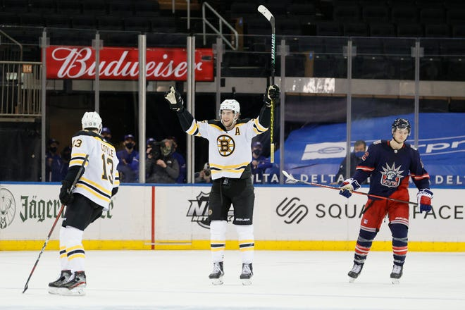Bruins defenseman Brandon Carlo, center, reacts after teammate Charlie Coyle, left,  scores during Sunday's third period, as the Rangers' Julien Gauthier looks on.