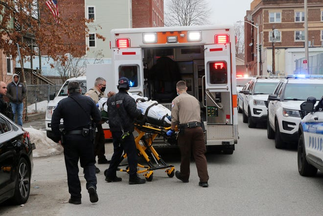 An apparent victim of gunshot wounds is transported by EMS from a home on Piedmont Street in Worcester on Sunday.