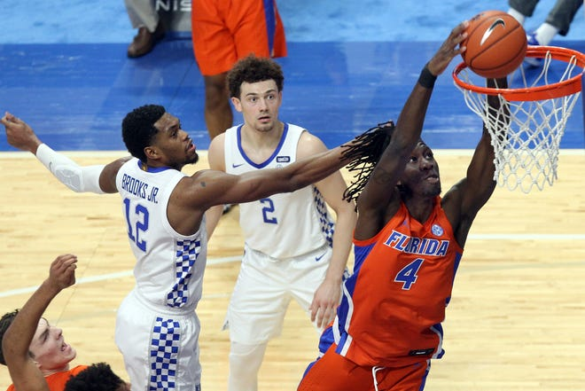 Florida's Anthony Duruji dunks near Kentucky's Keion Brooks Jr. (12) and Devin Askew (2) during the first half Saturday in Lexington, Ky.