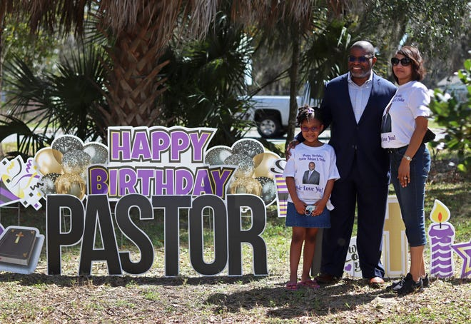 Pastor Adrian S. Taylor poses for a photo next to one of the Happy Birthday signs with his wife, Dr. Courtney Taylor, and their daughter, Alexis, after the drive-thru celebration parade for his birthday and 16th pastoral anniversary at Springhill Baptist Church on Sunday. [Lauren Witte/Special to the Guardian]
