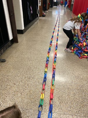 """Chain links line a hallway at New Philadelphia's Central Elementary as students show off some of the construction paper chain links made for this year's theme of """"Rainbow Links for the Rainbow Connection."""" Principal John Zucal estimates the links could circle the entire building twice."""