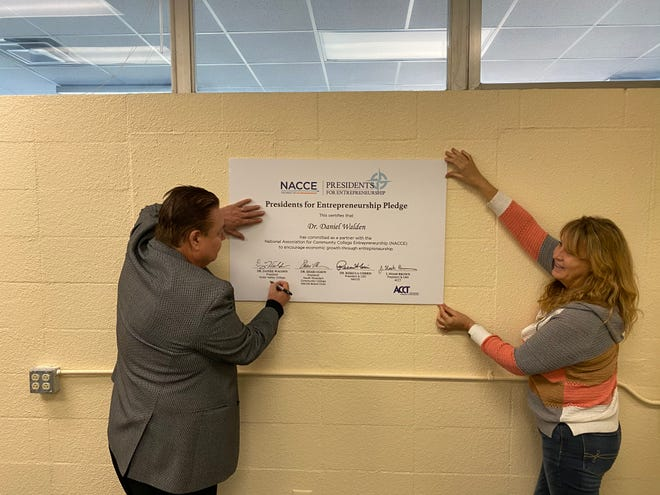 Victor Valley College President/Superintendent Dr. Daniel Walden signs the Presidents for Entrepreneurship Pledge with support from his executive assistant, Michelle Painter.