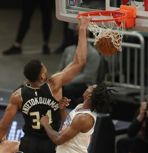 Bucks forward Giannis Antetokounmpo dunks over Clippers guard Terance Mann during the second quarter.