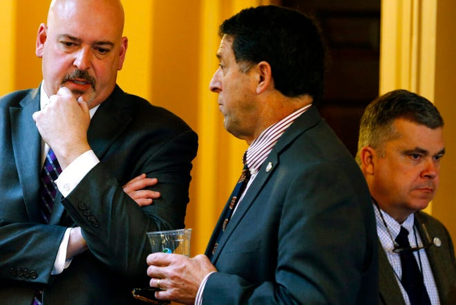 """FILE - In this Wednesday, Jan. 16, 2019 file photo, Del. Dave LaRock, R-Loudon, center, speaks with House majority leader Del. Todd Gilbert, R-Shenandoah, left, during a House session at the Capitol in Richmond, Va. LaRock, who attended the Trump rally that preceded the Jan. 6, 2021 attack on the U.S. Capitol, warned a House Healthcommitteein late January 2021 that COVID-19 vaccines could not be trusted. He said they were especially risky for several communities, including the elderly and people of color. Democratic Del. Cia Price, who is Black, called LaRock's false claims """"simply dangerous.""""(AP Photo/Steve Helber)"""