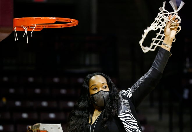 Missouri State Lady Bears head coach Amaka Agugua-Hamilton raises the net into the air on Saturday, Feb. 27, 2021, after a net cutting ceremony for winning the Missouri Valley Conference at JQH Arena.