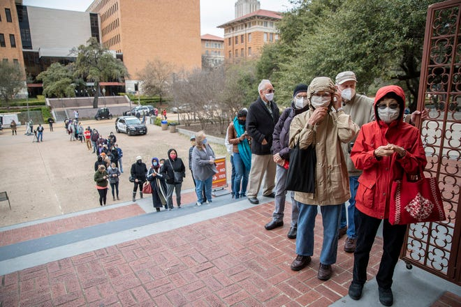 Hundreds of people with appointments wait in line to receive the COVID-19 vaccine at Gregory Gymnasium on the University of Texas campus Monday.