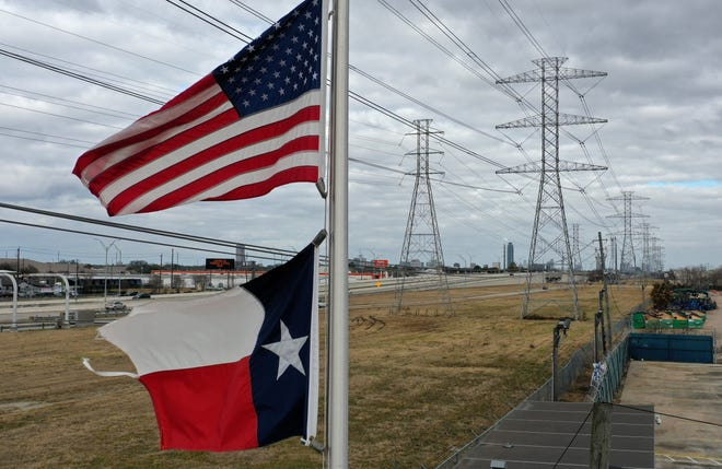 The U.S. and Texas flags fly last month in front of high voltage transmission towers in Houston. (Justin Sullivan/Getty Images/TNS)