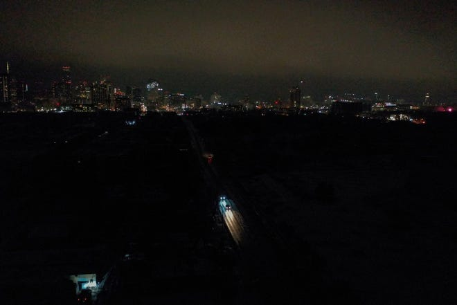 Vehicles drive down East 7th Street as power outages continue to darken most of East Austin on Wednesday, Feb. 17, 2021.