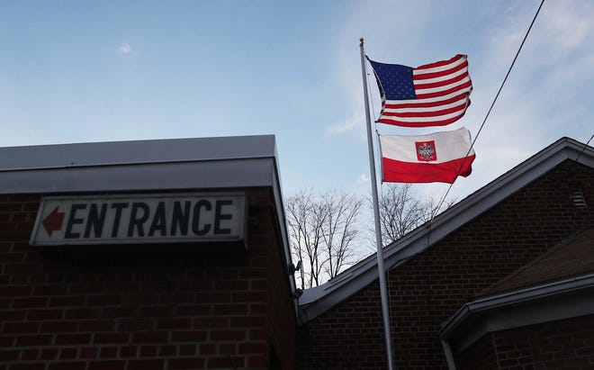 An American flag flies over a Polish flag with a coat of arms at the Polish American Citizens Club in Akron.