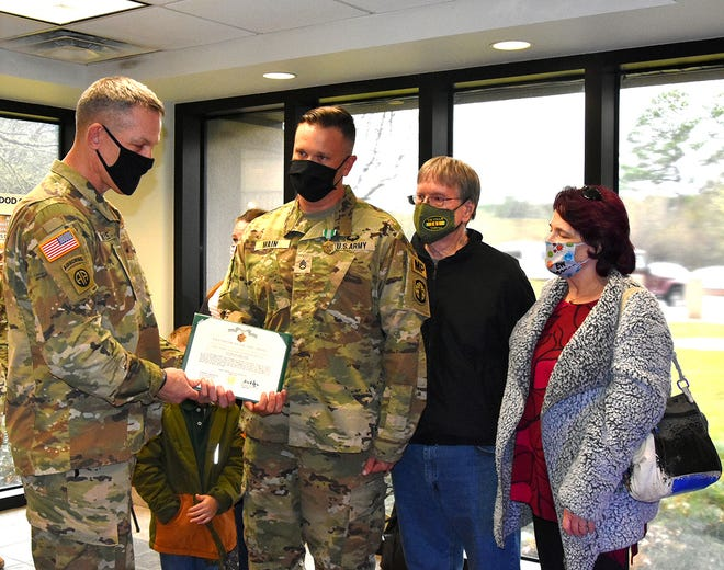 Brig. Gen. David S. Doyle (left), Joint Readiness Training Center and Fort Polk commanding general, presents Staff Sgt. Herman Main (second to the left), 204th Military Police Company, 519 MP Bn, with the Army Commendation Medal for saving a child's life, Jan. 16, at the Main Post Exchange while he was shopping. Pictured with Main are his parents Herman Main (second to the right) and Kathy Main (right).