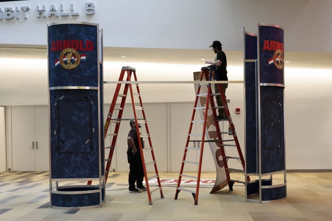 Workers tear down signage for the Arnold Sports Festival expo last year after event organizers and state officials agreed to cancel the trade show and limit spectators amid concerns about spreading COVID-19.