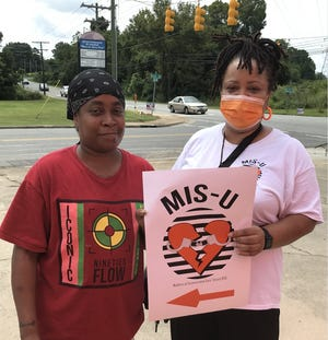 Frankie Reid (right) stands with someone who visited the booth for Mothers of Incarcerated Sons United 26 at one of their tabling events.