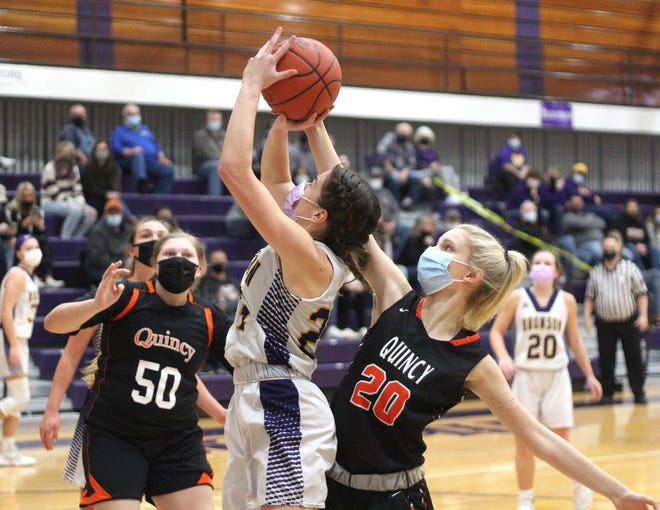 Bronson's Jenna Salek goes up strong in the paint but Quincy's Ella Dunn (20) is there for the block. Quincy's Alissa McCavit (50) looks on.