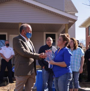 Dansville native Heather Madonia is presented with ADT's LifeSaver Award outside the Joplin, Mo. home she helped save as the Whitlock family and Joplin first responders look on.