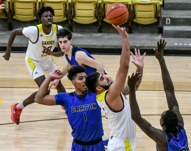 Garden City Community Colege's Jasman Sangha, center, goes up for a basket in the lane against Barton County Feb. 24 as teammate Mohamed Diarra, left, looks on at Perryman Athletic Complex.