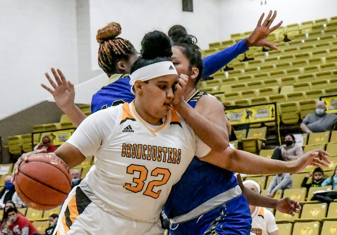 Garden City Community College's Elizabeth Sherrill takes a hand to the face as she drives around Barton County's Gabby Flute Player for a basket Feb. 24 at Perryman Athletic Complex.