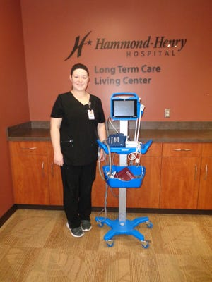 Nicole Kittelson, RN and Long Term Care Manager, shows the Dinamap monitoring equipment purchased by the HH Hospital Auxiliary with funds from the Lovelight Tree Project.