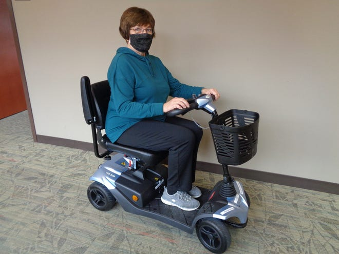 Hammond-Henry Hospital Auxiliary board member Mary Jane Causemaker is shown on one of the two four-wheel electric scooters that were purchased with funds from the Auxiliary Lovelight project.