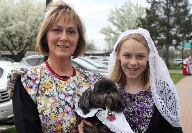 Stephanie Beyer, left, and Ashley Cramer, 11, hold KuaNi the dog before the Tulip Time Volksparade. The pair and KuaNi participated in the Dutch Dogs portion of the parade.