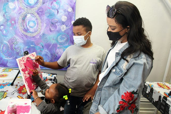 Breauna Cain, right, watches as her son Braylon Cain and daughter Ereauna Patterson paint a picture at a Super Hero paint party on Saturday, Feb. 27, 2021, at J & S Studio in Freeport.