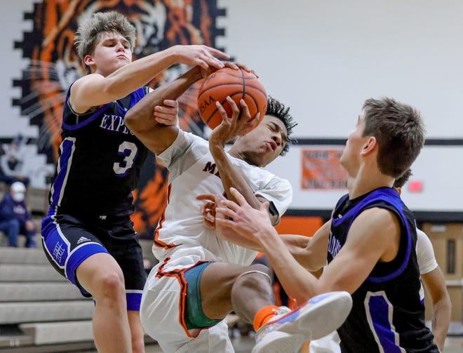 Hudson's Ryan Evan fights Massillon's Ardell Banks for a rebound during the Explorers' 56-33 loss to the Tigers' Saturday.