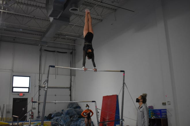 Aurora freshman Hannah Salgado competes on the bars.