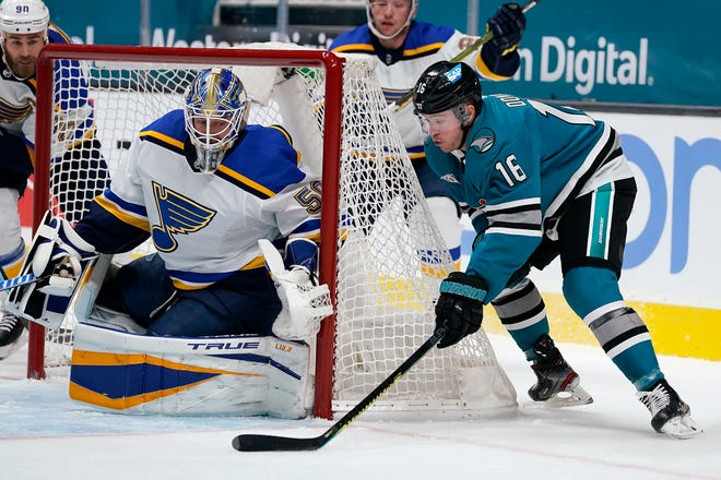 St. Louis Blues goaltender Jordan Binnington (50) blocks a shot by San Jose Sharks center Ryan Donato (16) during the first period of an NHL hockey game in San Jose, Calif., Saturday, Feb, 27, 2021.