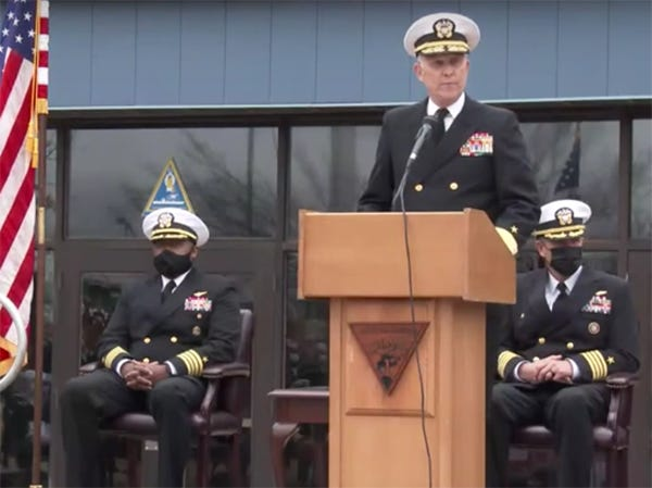"""Retired Navy Rear Adm. Greg Slavonic gives opening remarks. during a change of command ceremony held Friday afternoon. Slavonic presented retiring United States Navy Capt. Anthony """"Tony"""" Barnes with the Legion of America award. Seated, left to right: U.S. Navy Capt. Cedrick L. Jessup, United States Navy Capt. Anthony """"Tony"""" Barnes"""