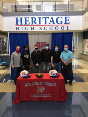 Heritage High School senior football players Tyler Miranda (second from left), Haydon Wiginton, Briley Green and Cullen Stone pose for a photo last Wednesday during a signing ceremony at HHS. Also pictured are HHS head football coach and athletic coordinator Lee Wiginton (left) and MISD athletic director Todd York (right). Haydon Wiginton will play football for Oklahoma State, while Miranda and Green will play for Southwestern Assemblies of God University and Stone will play for Tyler Junior College.