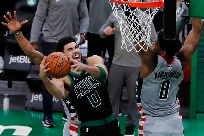 Boston Celtics forweard Jayson Tatum shoots the go-ahead basket against Washington Wizards' Rui Hachimura (right) during the second half of an NBA basketball game Sunday in Boston.