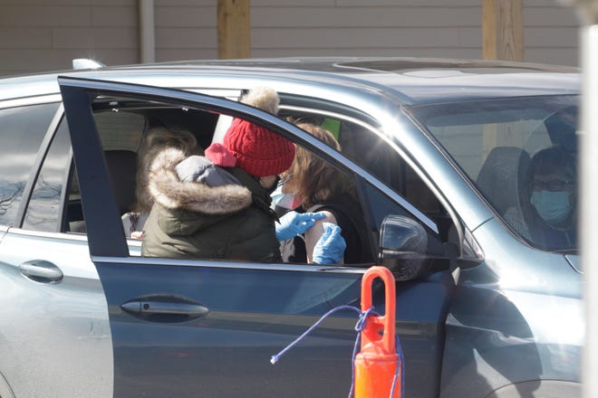 A volunteer healthcare worker administer's a second round of the Pfizer vaccine shot to a patient that attended Randolph County's COVID-19 drive-thru clinic held Feb. 24 at Moberly's Rothwell Park.