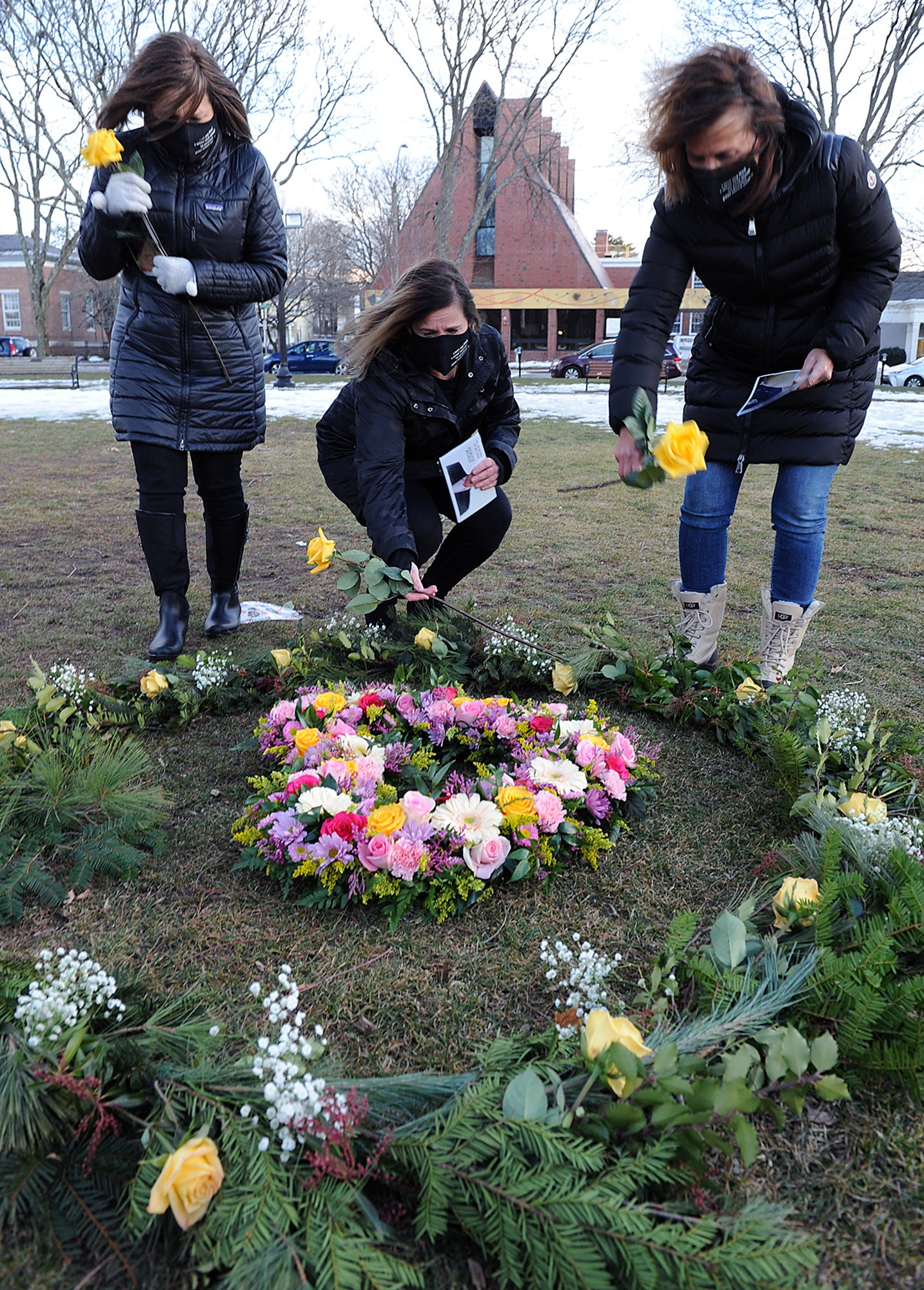 Massachusetts residents Jill Federman, of Hingham, Lisa Mazerolle, of Easton, and Michelle Pepe, of Sharon, all lost their fathers to COVID-19. They place yellow roses and photographs on the Floral Heart Project on the Natick town common on March 1, 2021.