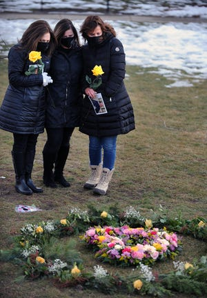 Jill Federman, of Hingham, Lisa Mazerolle, of Easton, and Michelle Pepe, of Sharon, all of whom lost their fathers to COVID-19, at the Floral Heart Project on the Natick Common, March 1, 2021.