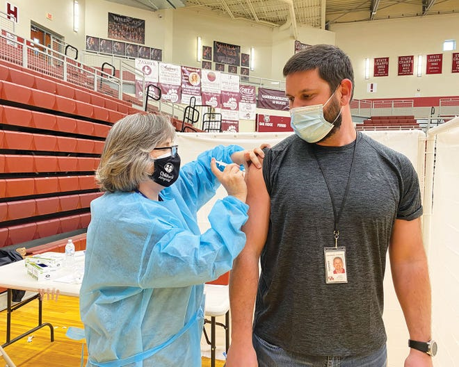 Holly Cross, Oak Ridge Schools/Special to The Oak Ridger Lori Gupton, Oak Ridge High School's nurse, vaccinates James Mitchell, of Jefferson Middle School, on Friday, February 26, 2021, at the high school during a vaccination clinic for all employees in the school system. In an online meeting with the Tennessee Press Association Monday, Gov. Bill Lee said 60,000 Tennesseans were vaccinated for COVID-19 last Friday.