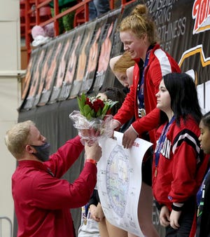 Ottawa's Darby Weidl's coach and brother Dalton Weidl, hands her roses, her medal and championship bracket after she wrestled Oskaloosa's Allison King in the 155 pound weight class championship of the KSHSAA Girls Div II State Wrestling Tournament at the Tony's Pizza Events Center in Salina Friday, Feb. 26, 2021.