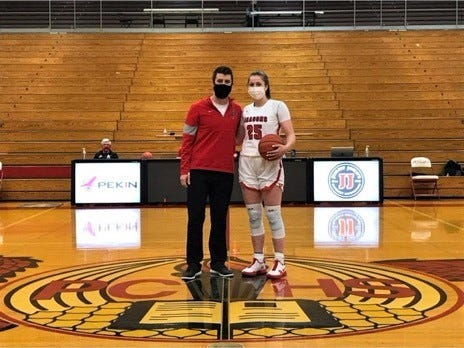 Pekin girls basketball coach Brett McGinnis  presents the game ball to Dragons star Taylor Goss on Saturday after Goss scored her 1,000th career point for Pekin on a three-point shot against East Peoria.