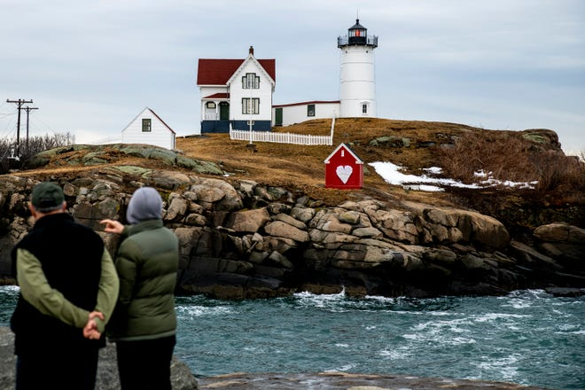 John and Jan Ferry of Portland visit the Nubble Lighthouse in Cape Neddick, Maine, on Monday, March 1, 2021. The town of York participated in the Floral Art Project, which recognized a national day of mourning for the lost lives to COVID-19.
