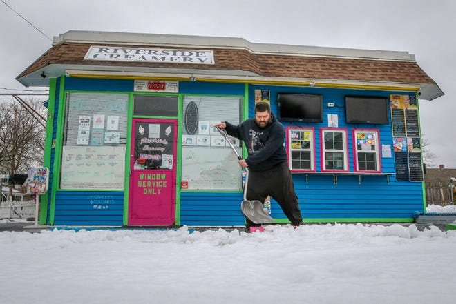 Alan Graves shovels the slushy snow in the front entry of Riverside Creamery in Riverside on February 2. The Providence area was below normal for snowfall in December and January but a snowy February put it above average for the season, according to the National Weather Service.