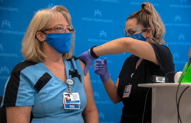 (12/17/20) Registered nurses Sandra Heinze, left, receives a Pfizer COVID-19 coronavirus vaccine shot from LVN Hannah Serrano at the Kaiser Permanente clinic in Manteca.