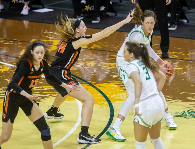 Oregon's Sedona Prince, with ball, looks for an opening against Oregon State's Taylor Jones, second from left, during Sunday's game at Matthew Knight Arena.