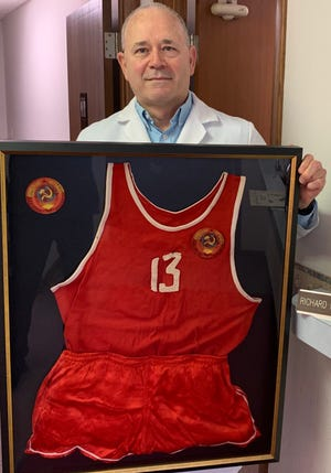 Salinan Richard Bradbury holds the USSR basketball jersey that was given to him by Soviet player Mikhail Korkia and a patch he received from head coach Vladimir Kondrashin at the team's 1975 exhibition game at Marymount College in 1975.